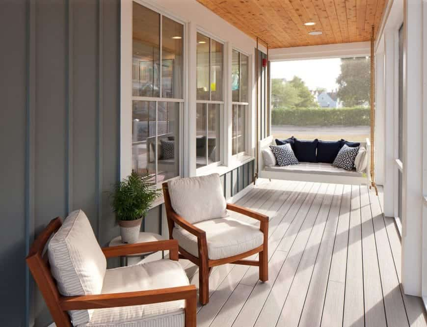 This porch boasts of elegance and grace. It has ash-white wooden flooring, a crisp white sofa with a variety of cushions, white windows with square glasses and a fancy grey wall design on one side. It is also a very rich and modern design that would add true allure to the house entrance.