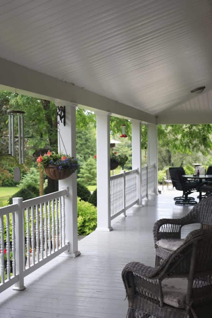 This porch looks like it has come right out of a movie. White ceiling, railings, and blackish cane chairs give it a very contemporary touch. The addition of stunning hanging flower pots adds to the beauty of it as the porch leads into a beautiful garden.