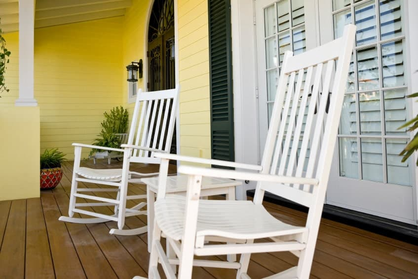 Simplicity seems to be the main focus of this porch with white chairs, wooden flooring, pale yellow painted walls, and small planters tucked away in a corner.