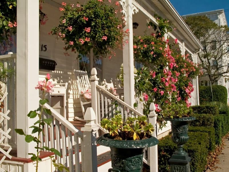 Truly picturesque at its best, this design is an absolute feast for the eyes. With gorgeous dangling flowers, plants in the front and stark white railing, it makes a beautiful porch.