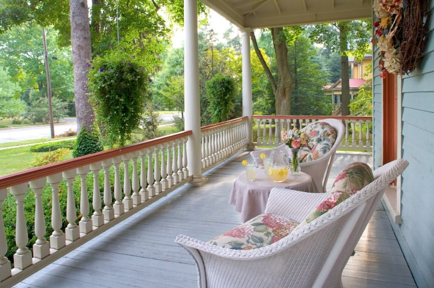 For those in search of a simple yet elegant porch design, this is the one. It has small white railings with a wooden top and two decent white chairs with fancy pillars to give it a very graceful touch.