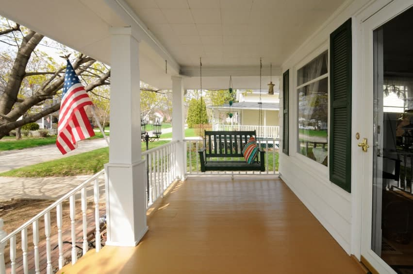 This has to be one of the most elaborate porches in the list. With a vast walkway kind of a space leading to a pretty porch swing and white railing on the side, all of it combined makes the space look very attractive.