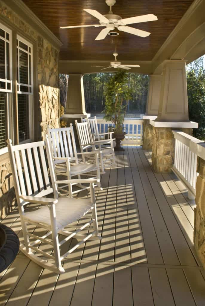 With white chairs, white fans, white railing, and windows, this design is simple but unique. Sporting a wooden look otherwise, the combination of white with brown makes it look very appealing