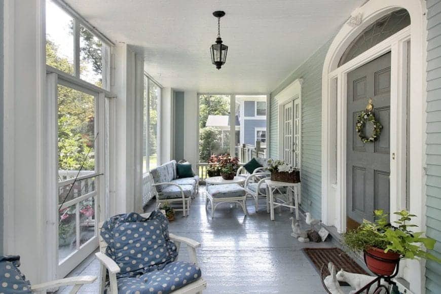 If sophistication had an image, it would probably be in the form of the picture of this porch. It is a classic white porch, with an extensive seating arrangement, large windows that allow proper outdoor views and ash-grey flooring, adding to the elegance of it.