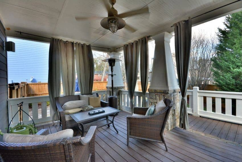 This looks more like a fancy veranda with a fan, a grand seating affair, curtains all around and wooden flooring. It is also super lavish and contemporary; making it look like it came right out of an interior magazine.
