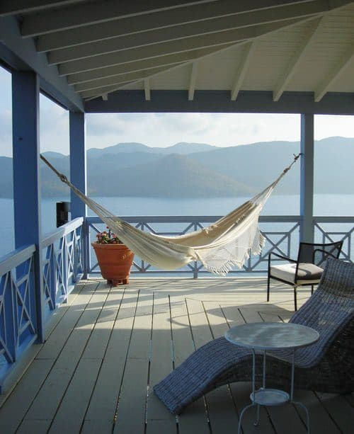 Looking more like the entrance outside a hut at the beach, this porch is just fantastic. Sporting a blue color theme and a comfortable white relaxing swing, along with a fancy relaxing chair, it is just magnificent.