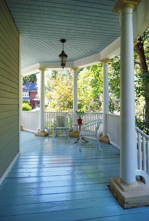 This porch makes use of a wide open space and has only two seating chairs, which make it look very simple and spacious. There are tall pillars attached to the railing in the front, offering a gorgeous view of the outdoor nature.