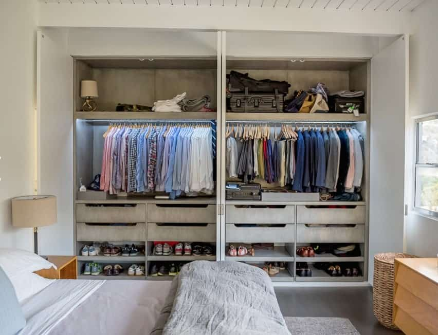 This lovely room is decorated in shades of pastel gray, pink and teal, but the highlight of the room is the open concept closet, immaculately organized with feminine goodies. The creamy white tones of the closet are offset by the warm rich color of the flooring and the golden lamps hanging from above. This is a perfect dressing space for a young lady of fashion.
