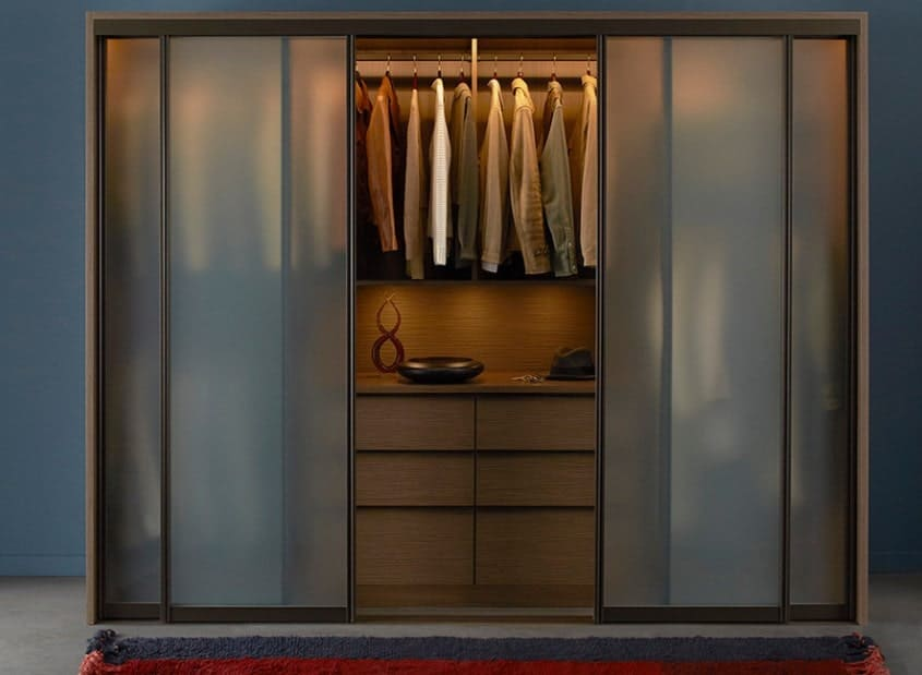 This very urban and modern closet exudes an air of mystery. The glass sliding doors are smoky and translucent and open to reveal an interior made of golden wood. Several spotlights in the closet give the wood a warm glow. Several antique-looking objects and an Indiana Jones-style hat give the illusion of the owner being a man of adventure and mystery.