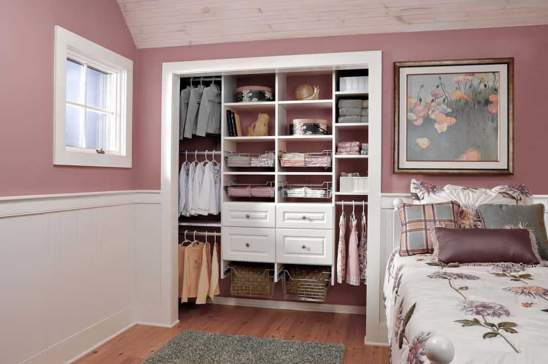 This super pretty floral bedroom is every young girl's fantasy — and so is the accompanying closet. The bedroom is painted in beautiful dusty rose pink with a bed with a flower-printed sheet and a floral painting hanging above it. The pale cream color closet matches the color of the lower wall and perfectly showcases all the frills and frippery that a girl could ever want.