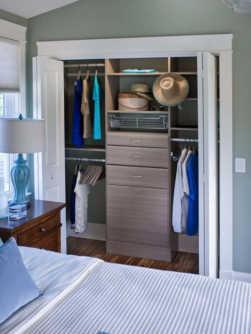 Cool and casual, this reach-in closet is the perfect accompaniment to a beach house bedroom. The closet has white doors and trims. It comes with a grey-brown set of drawers that mimic the look of beach sand. The room reflects ocean colors like aquamarine and turquoise and the hanging sunhats and loose blouses give the perception the beach is just outside.