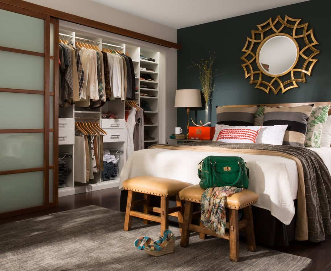 This reach-in closet stands in perfect harmony with the bedroom it is installed in. The closet has soft white lines which provides a very pleasing and balancing effect to the bedroom, which has a bold teal-gray accent wall and a large mirror with an ornate and gilded frame. The closet's pale teal tinted sliding doors are a lovely match with the wall. This closet has lots of character and personality.
