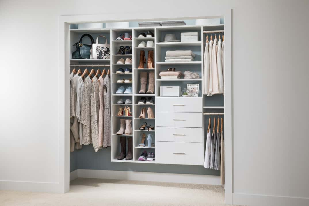 This wonderful built-in closet is perfect for a woman who loves to work but has her share of traveling and adventure too. The closet is trimmed in eggshell-white with the back of the closet in a solid dove gray color. Although it is free from frippery, it has plenty of shelves to accommodate everything a woman wants.
