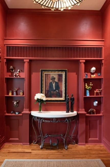 An elegant foyer featuring a classy man's photo framed on the red wall. The hall is lighted by a stylish pendant light.