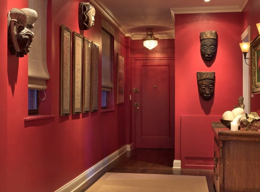 This foyer features matte red walls with plenty of fine wall decors lighted by pendant and wall lighting.