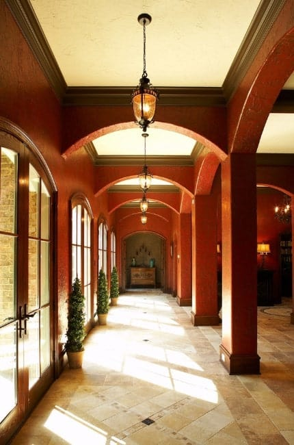 This elegant foyer features tiles flooring, arch hallway lighted by pendant lights.