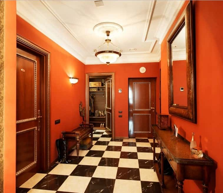 Foyer featuring checker sparkling checker flooring, red walls and a white ceiling, all lighted by a pendant and wall lighting.