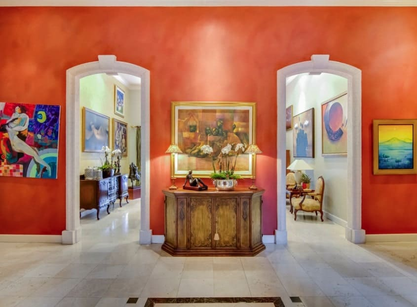 Foyer with artistic decors on the red walls. The tiles flooring looks perfect with the foyer's style.