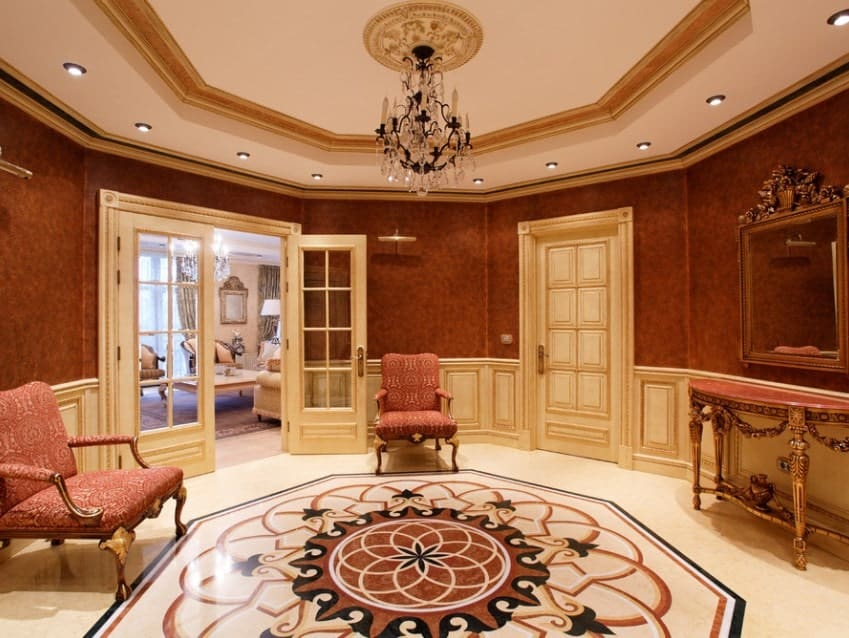 Both the red walls and the flooring look so elegant in this foyer. Added by its circular ceiling lighted by recessed lights and chandelier and it's so jaw-dropping.