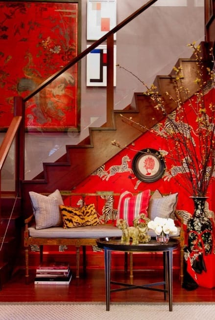 This red foyer offers a Chinese vibe in it. The designs and decors are artistic and the glass staircase railings add elegance to it.
