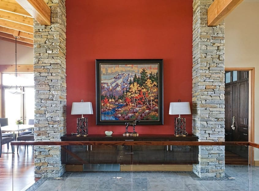 This foyer features brick pillars and a red wall styled by a classy wall decor.