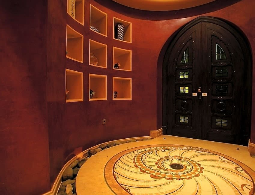 Gorgeous foyer with artistic flooring, stylish red walls and classy dark wooden door.