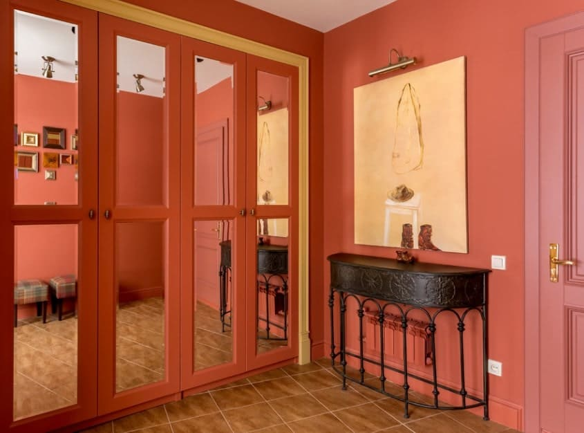 Foyer with tiles flooring and red paint all over the place. The french doors add style to the home's foyer.