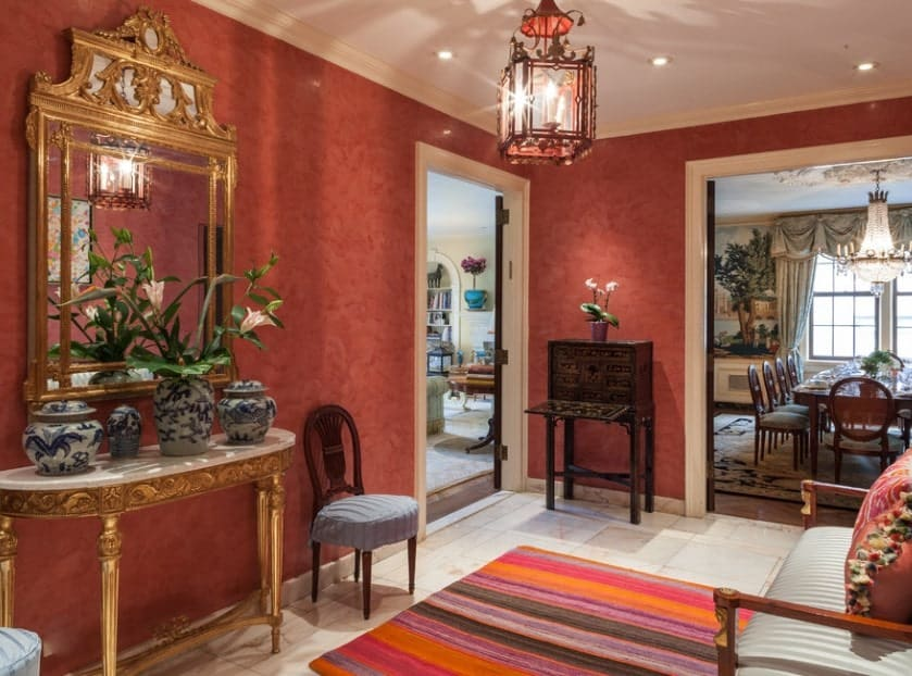 This elegant foyer features classy red walls and a charming chandelier lighting up the area.