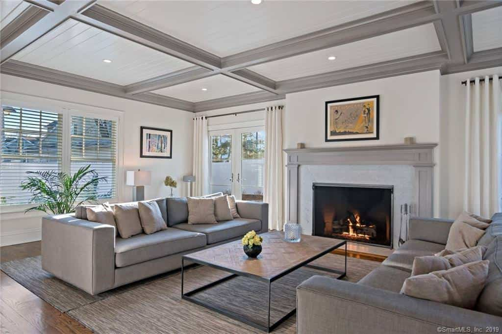 The formal living room is large and is furnished with two matching sofas.  The gray sofas match nicely with the coffered ceiling beams, gray fireplace mantle and gray area rug on hardwood flooring.