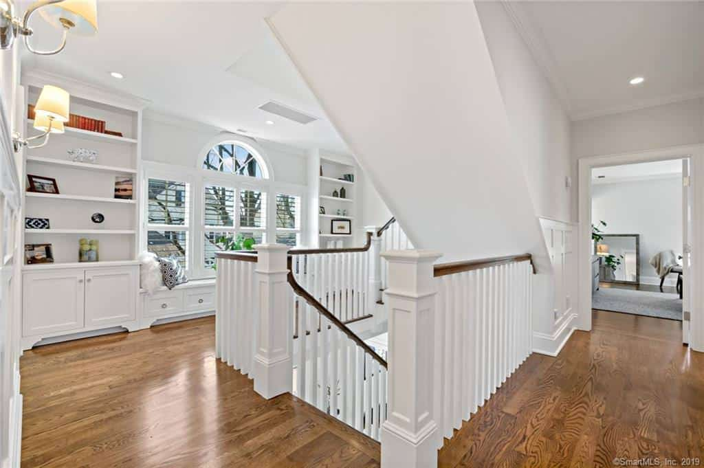 I absolutely love this second floor landing which is a room unto itself with window reading nook, custom wall shelves and large aisles for navigating to one of 3 bedrooms on this floor.
