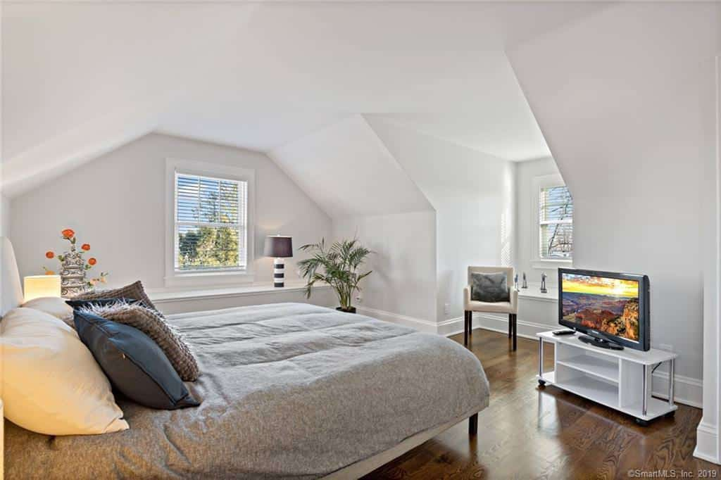 Check out this amazing attic bedroom with small sitting area, angled walls and ceiling, yet sufficient height for standing upright.