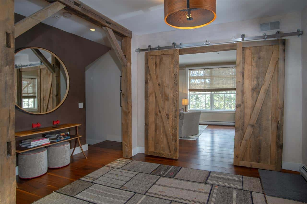 This farmhouse foyer features a hardwood flooring topped by a stylish rug. The sliding wooden doors are absolutely eye-catcher.