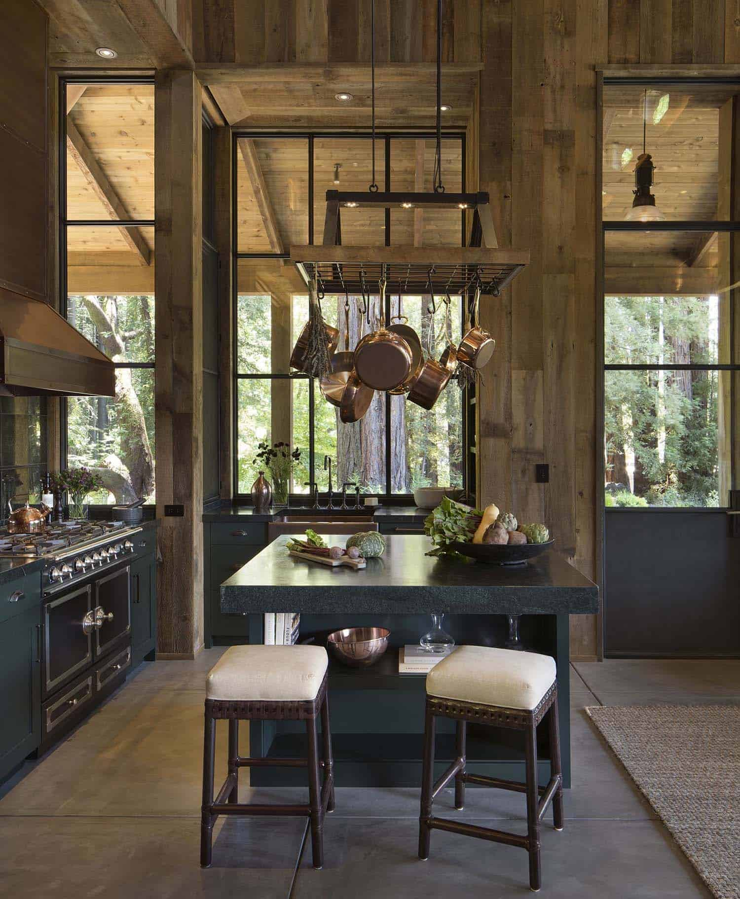Like the living room, the rustic kitchen has soaring ceilings. The extensive woodwork extends into the kitchen space that includes dark green cabinetry, a pot rack suspended above the island.