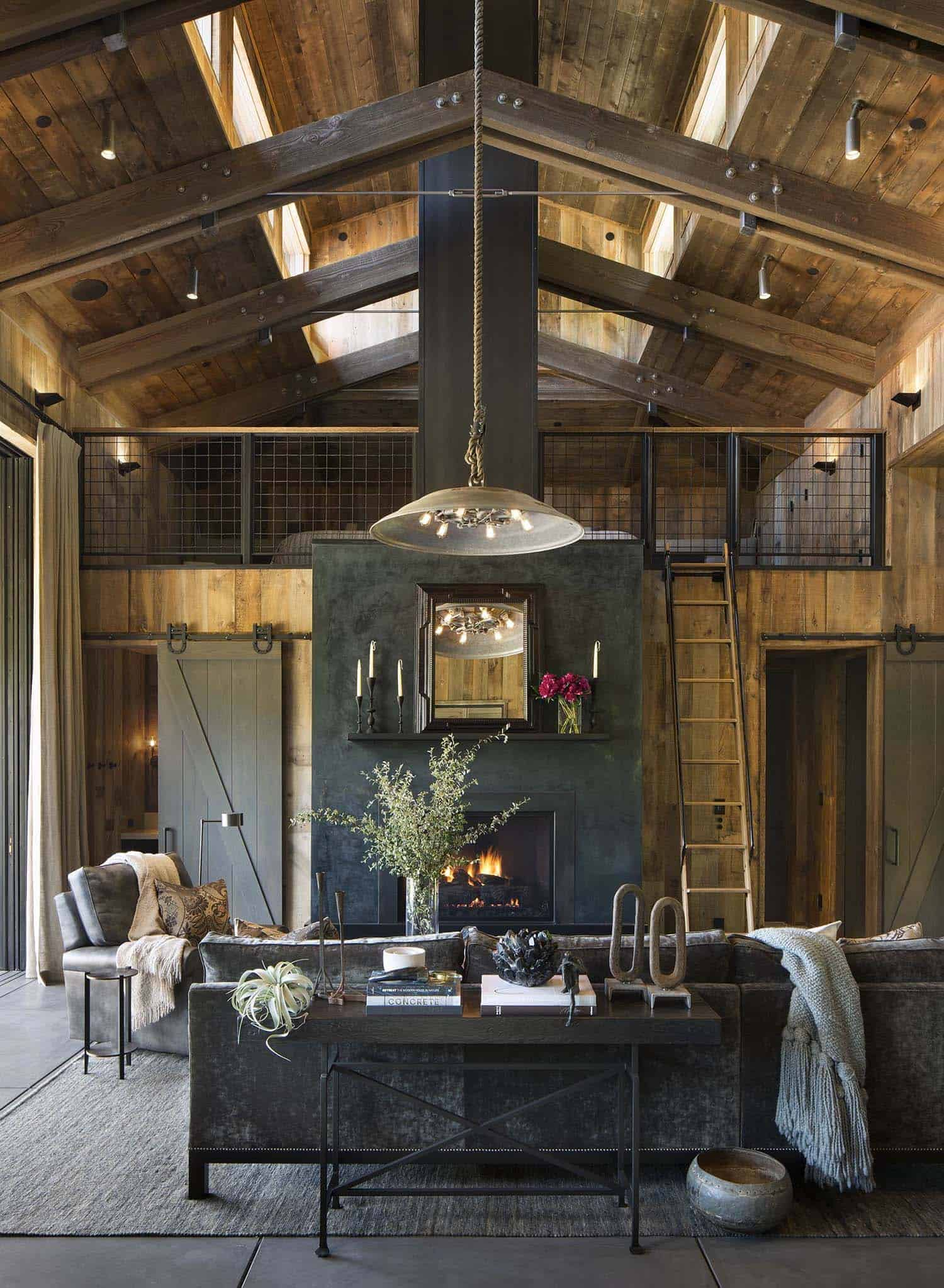 The rustic living room looks up to a cathedral ceiling with large wood beams with a barn style roof with upper windows shedding light onto the entire space. One side of the living room has a ladder leading up to a loft area looking down on the living space.