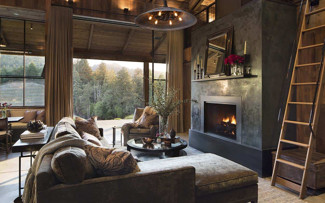 The main seating in the living room is a large, rustic sectional sofa (chaise lounge style) with an armchair in the corner. The seating is arranged around the large fireplace. There are large doors that lead to the covered porch/patio area outside.
