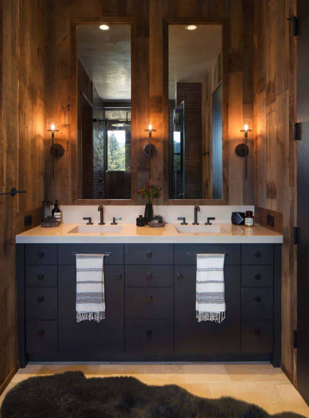The rustic bathroom has beautiful wood walls and a gray double sink vanity with two mirrors.