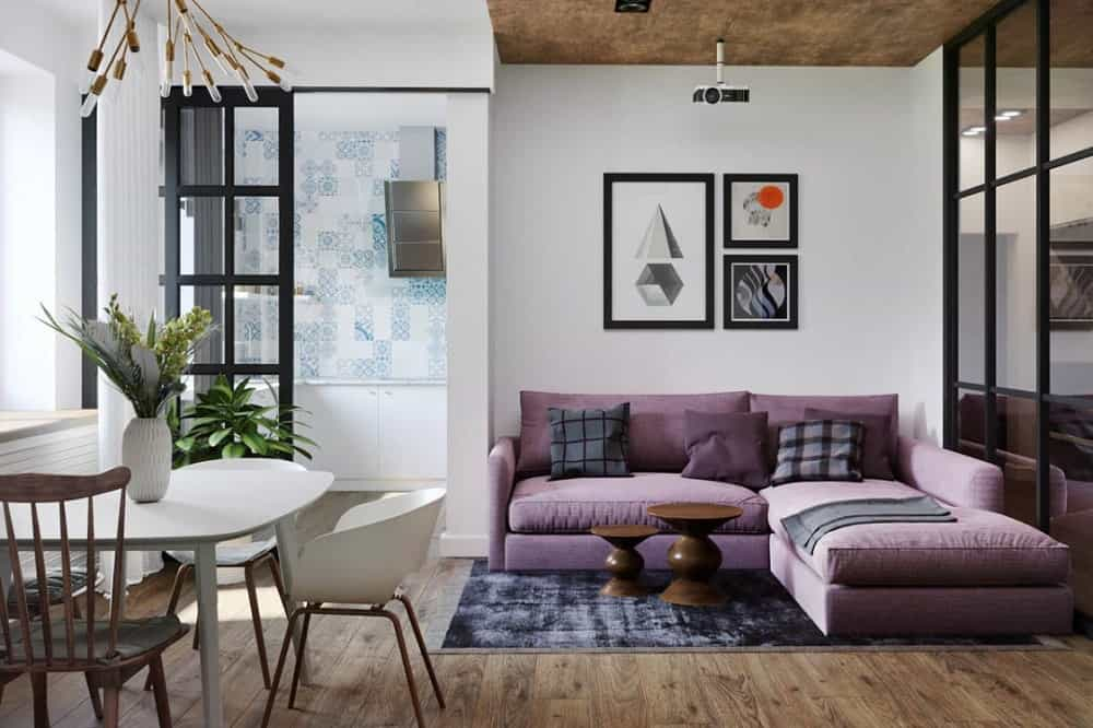 This is a look at the living room of the apartment with a large L-shaped purple sectional sofa next to the white dining set a few steps away. This was designed by Vagon Architects.