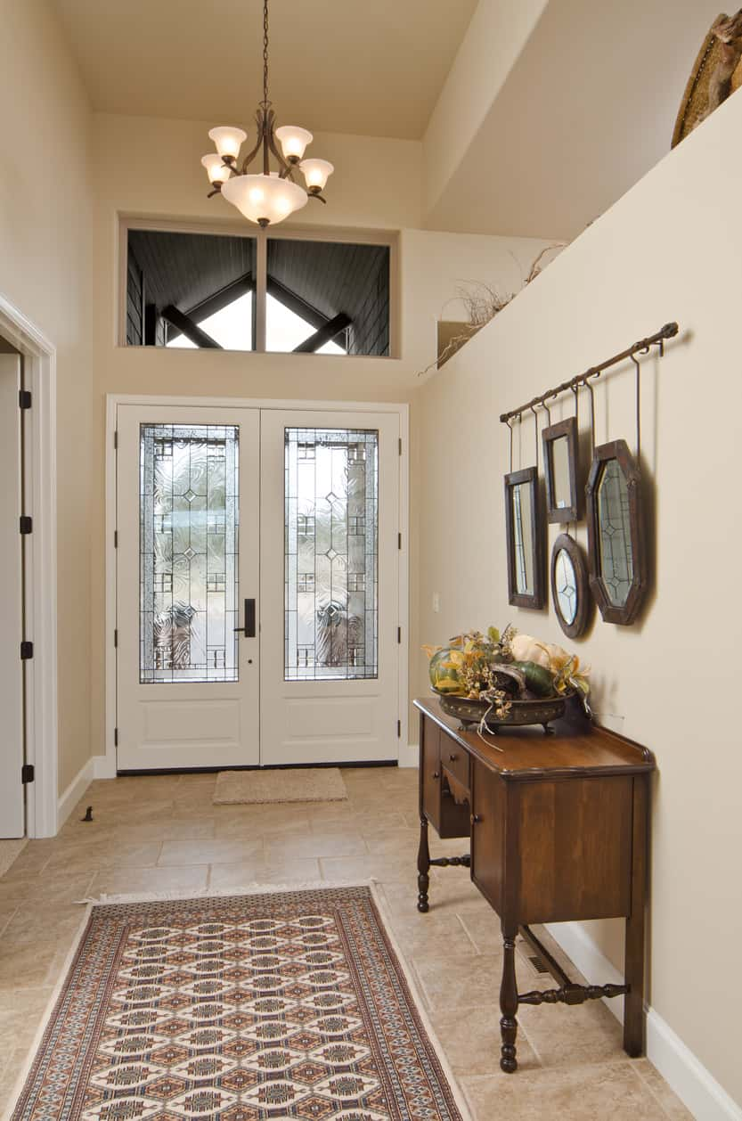 Small foyer with high ceiling. The elegant rug is set on the tiles flooring. The pendant light looks great with the wall color.