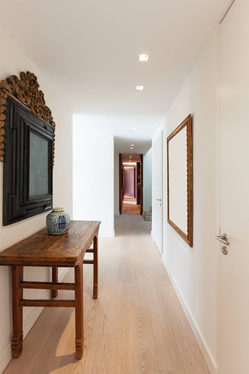 This small foyer features a classic combination of white walls and hardwood flooring added by elegant wall decors.