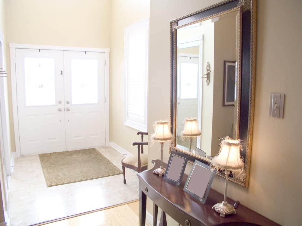 This bright small foyer features a light finished hardwood flooring and walls. The white doors and windows, along with the table lamps are so classy.