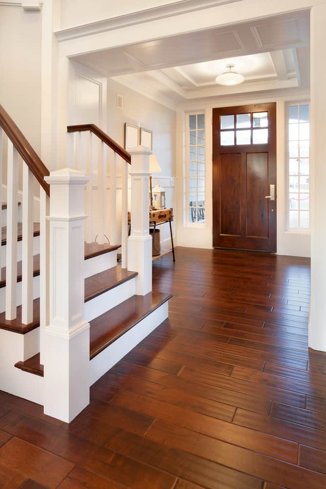 Small white foyer mixed with a rustic vibe. It features a hardwood flooring and staircase steps. The ceiling looks elegant as well.
