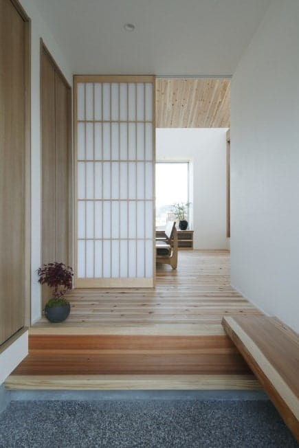 This foyer boasts a classy style with hardwood flooring and white walls, along with a Japanese-style sliding door.