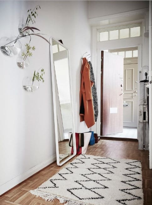Small foyer featuring a white walls and a linoleum flooring topped by a rug. The wall decors look refreshing.