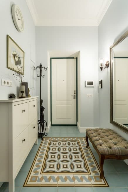 Small foyer with gorgeous tiles flooring and white walls. The wall lighting provides additional style.