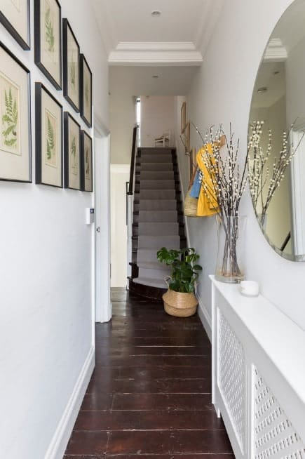 Narrow foyer featuring a hardwood flooring and white walls. Several decors on the wall add class to the hallway.