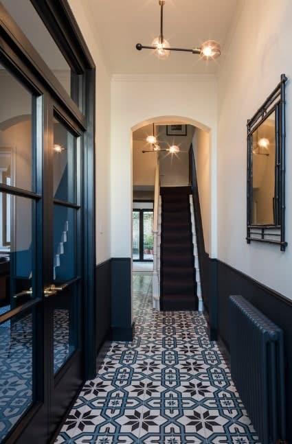Modish foyer setup with a very stylish flooring and beautiful combination of black and white walls. The doors are just magnificent.