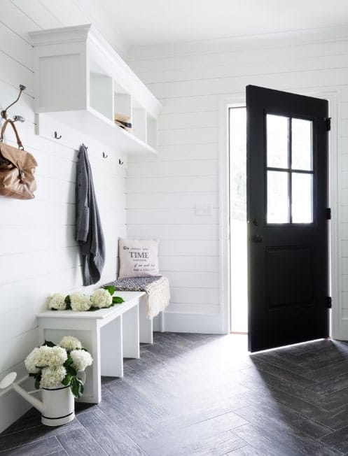 Beautiful small foyer with white walls added by a black shade. The hardwood flooring looks just perfect for the room's style.