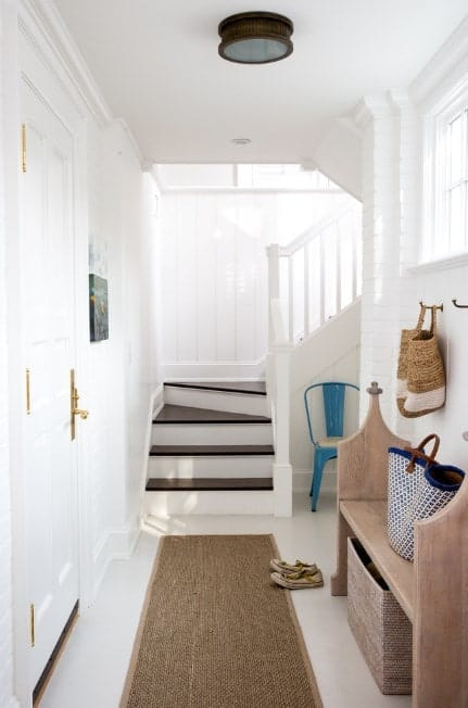 Small foyer featuring white walls and flooring topped by a brown rug. The staircase looks stylish with the dark finished steps.
