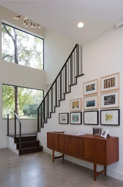 Small foyer featuring white walls and high ceiling. The wall offers multiple decors. The staircase features hardwood steps and iron railings.