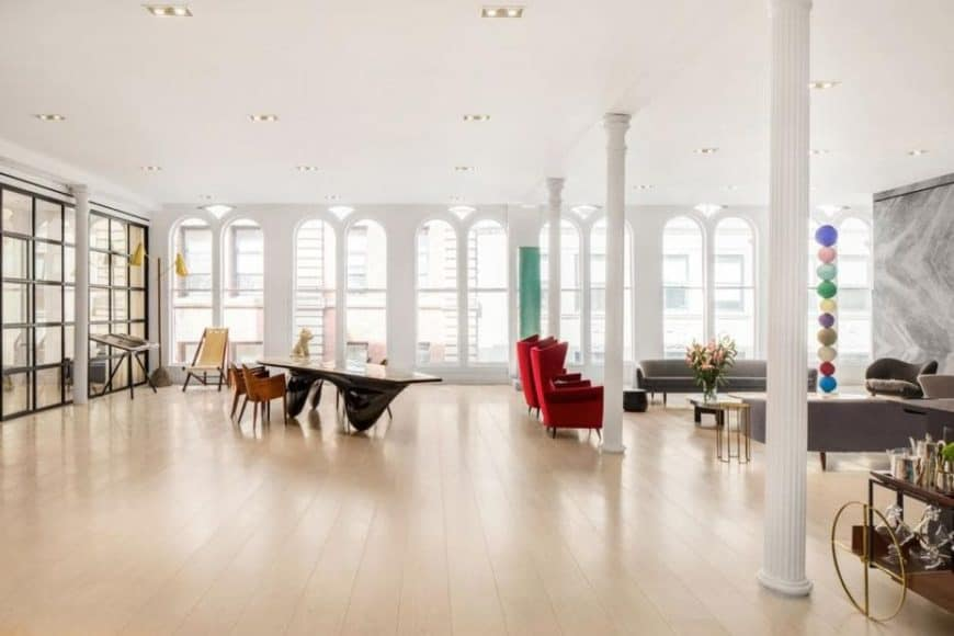 This is a look at the great room of the loft, It has a scious hardwood flooring that houses the dining, living and kitchen brightened by the row of tall arched windows. Image courtesy of Toptenrealestatedeals.com.